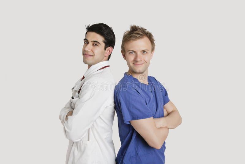 Ritratto dei professionisti di sanità che stanno di nuovo alla parte posteriore sopra fondo grigio chiaro fotografia stock
