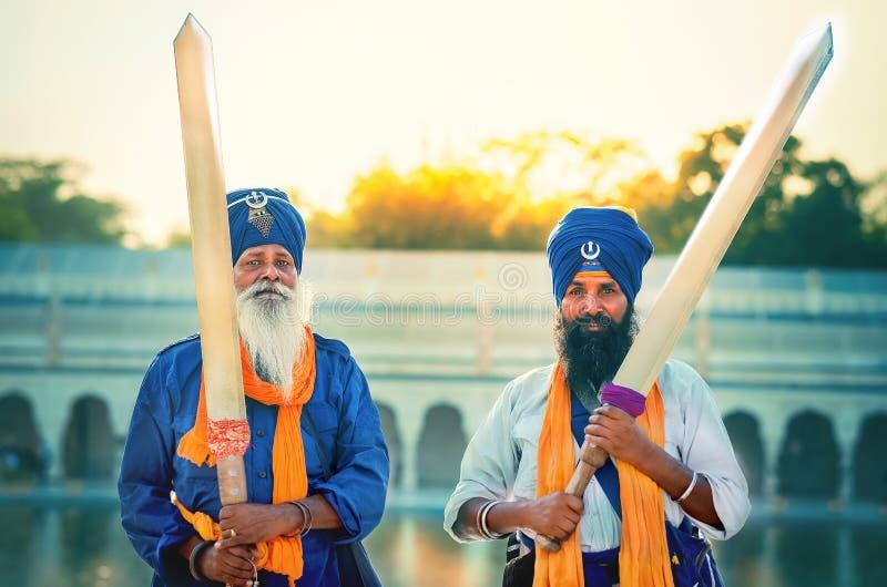 Ritratto dei protettori sikh dei guerrieri degli innocenti che giudicano le spade in mani all'alba di tramonto all'aperto fotografie stock libere da diritti