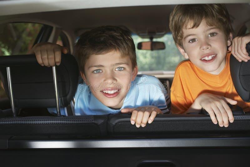 Ritratto dei ragazzi che sorridono in automobile fotografia stock libera da diritti