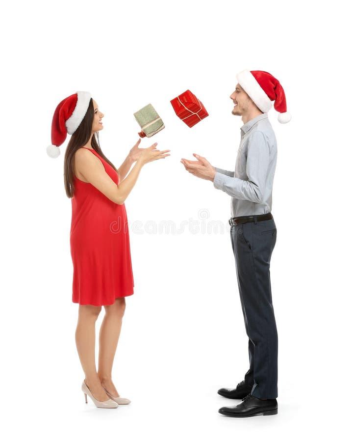 Ritratto dei regali di caduta di cattura di Natale delle giovani coppie sveglie su fondo bianco fotografie stock