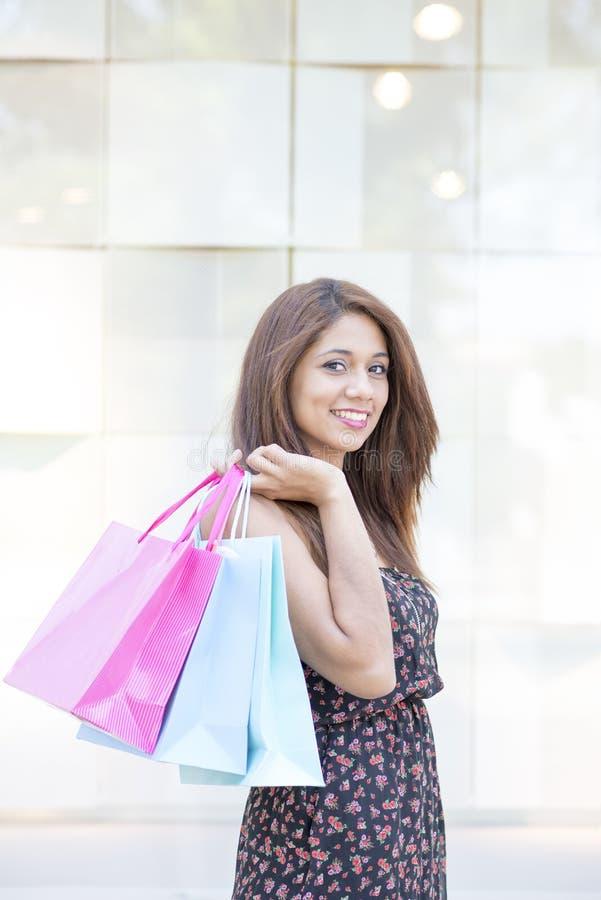 Ritratto dei sacchetti della spesa sorridenti eleganti della tenuta della donna fotografie stock