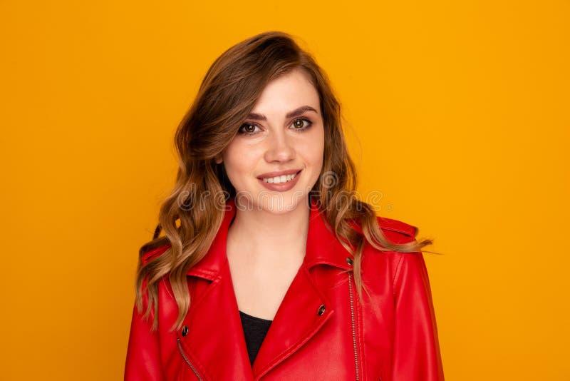 Ritratto dei vestiti graziosi della giovane donna in rosso isolati sopra i precedenti gialli immagine stock