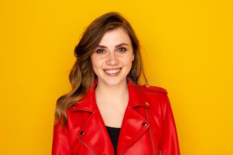 Ritratto dei vestiti graziosi della giovane donna in rosso isolati sopra i precedenti gialli fotografie stock