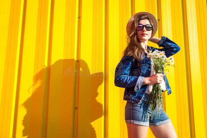 Ritratto dei vetri e del cappello d'uso della ragazza dei pantaloni a vita bassa con i fiori contro fondo giallo Attrezzatura di  immagini stock libere da diritti