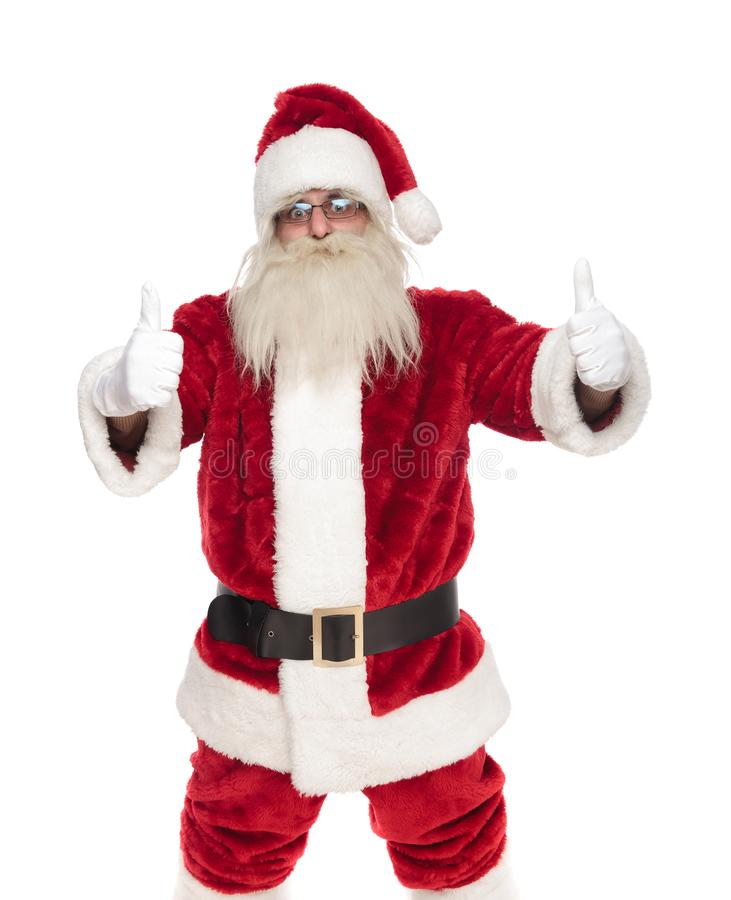 Ritratto del Babbo Natale con i vetri che fanno i pollici sul segno fotografia stock libera da diritti