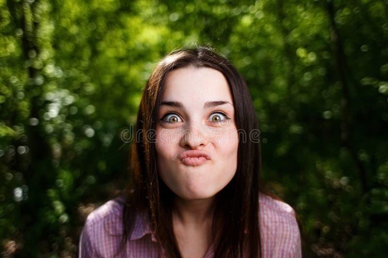 Ritratto del bacio di salto delle labbra della giovane donna sveglia, facente smorfie per il fu immagine stock libera da diritti