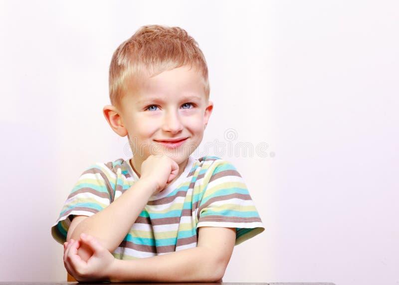 Ritratto del bambino biondo sorridente pensieroso del bambino del ragazzo alla tavola immagini stock libere da diritti
