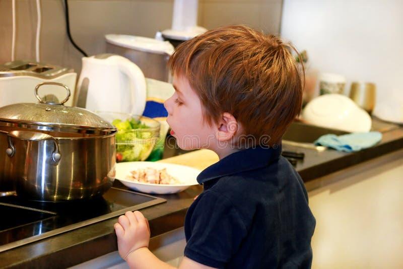 Ritratto del bambino in cucina Ragazzino sveglio, giocante nella cucina Il ragazzino ha fame, esamina e controlla  fotografie stock