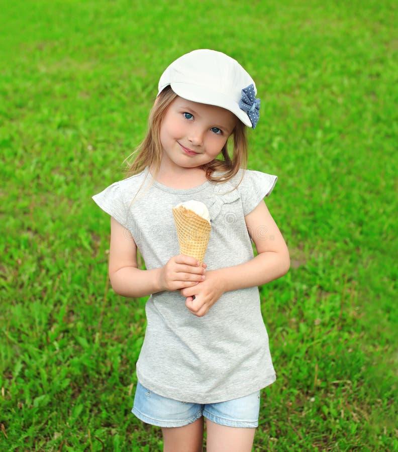 Ritratto del bambino della bambina in cappuccio con il gelato sull'erba immagini stock libere da diritti