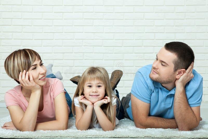Ritratto del bambino ed i suoi genitori che si trovano sul tappeto in salone Fondo bianco del muro di mattoni, spazio per testo fotografia stock