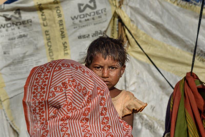 Ritratto del bambino indiano sulla via La gente povera viene con la famiglia alla città dal villaggio per lavoro Ed essi che vivo immagini stock libere da diritti