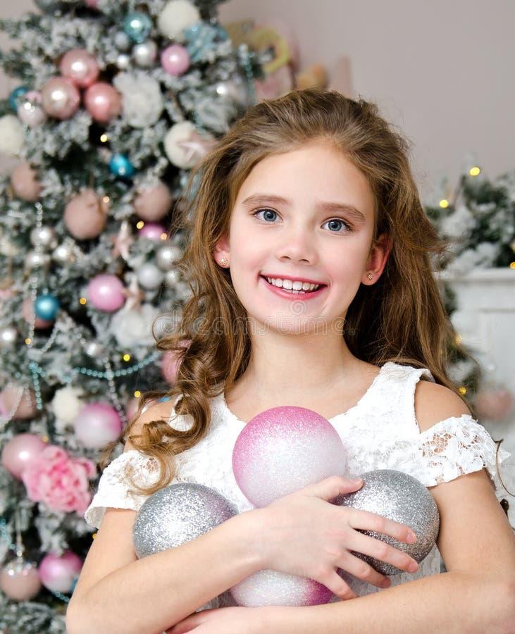 Ritratto del bambino sorridente felice adorabile della bambina in vestito da principessa che tiene le palle di natale fotografia stock libera da diritti
