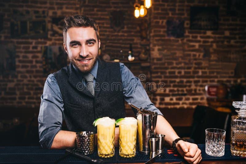Ritratto del barista bello professionista che sorride alla macchina fotografica, preparante i cocktail e servente le bevande fres immagini stock libere da diritti