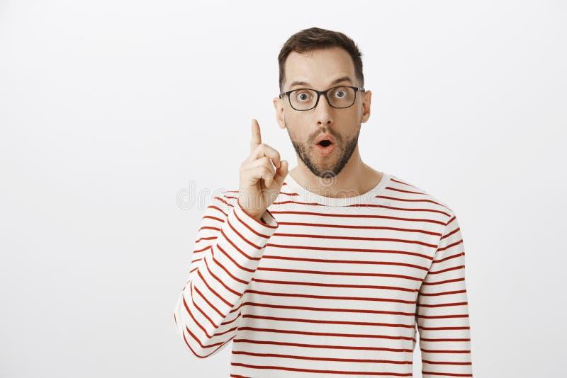 Ritratto del bel ragazzo emozionante in vetri neri, avendo idea ed alzando il dito indice nel gesto di Eureka, dividente immagine stock libera da diritti