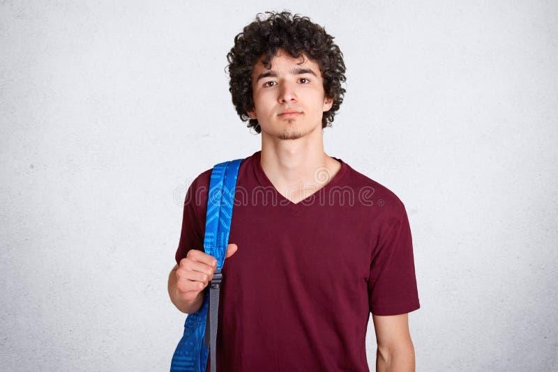 Ritratto del bel ragazzo premuroso con la condizione riccia dei capelli neri diritta, avendo zaino blu sulla sua parte posteriore immagine stock libera da diritti