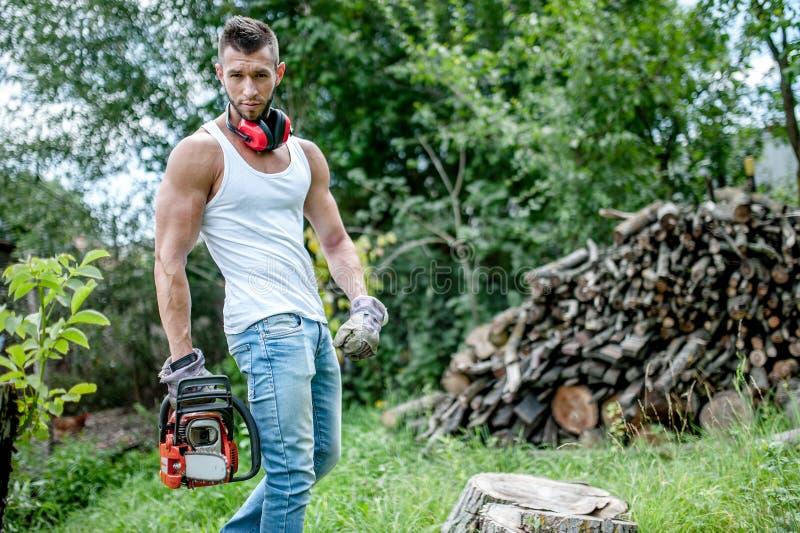 Ritratto del boscaiolo muscolare espressivo, uomo con la motosega immagini stock libere da diritti