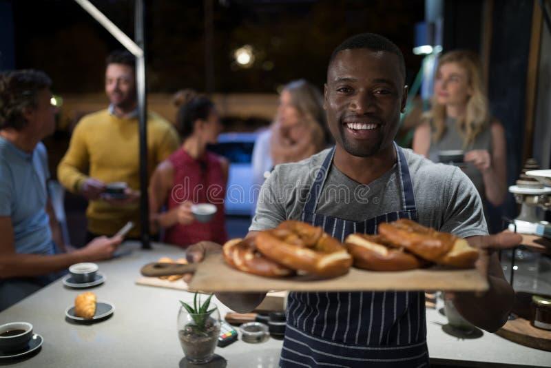 Ritratto del cameriere felice che tiene alimento dolce in vassoio di legno fotografia stock libera da diritti