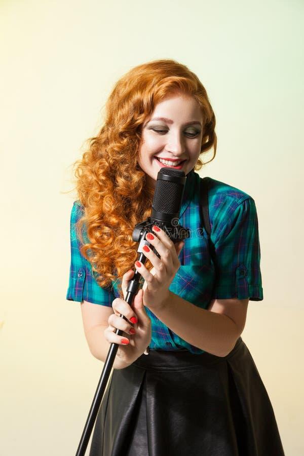 Ritratto del canto riccio-dai capelli della donna nel mic fotografia stock