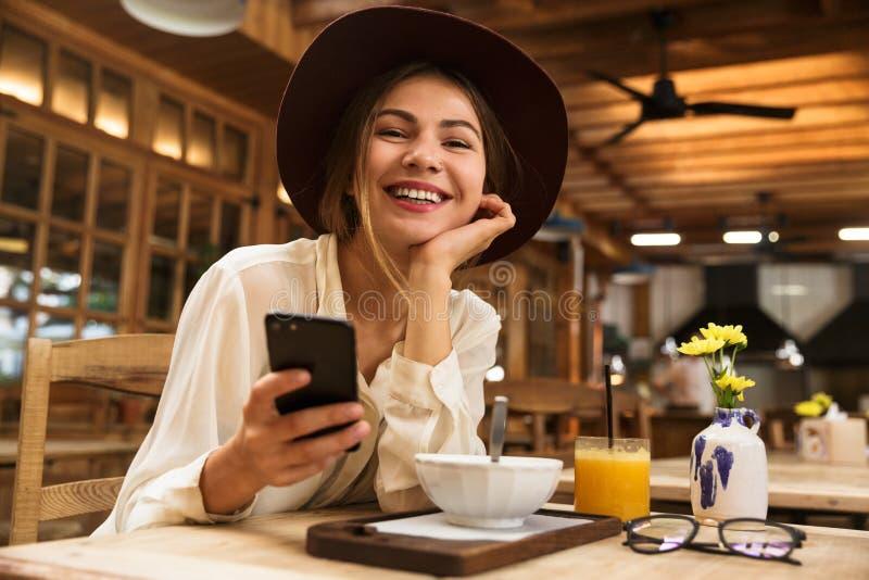 Ritratto del cappello d'uso della donna graziosa facendo uso del telefono cellulare fotografia stock