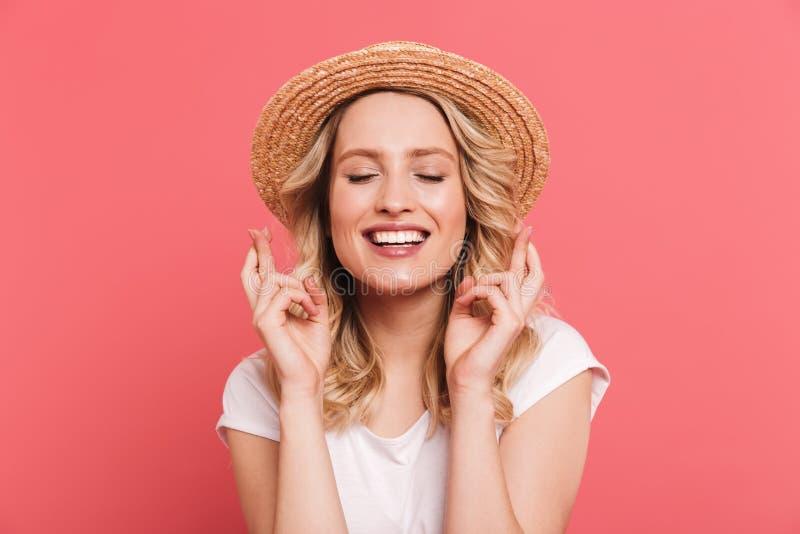 Ritratto del cappello di paglia d'uso biondo contento della donna 20s che tiene le dita attraversate e che desidera per la fortun immagine stock libera da diritti