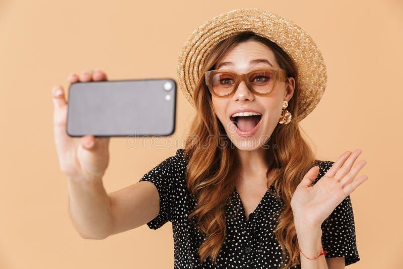 Ritratto del cappello di paglia della donna moderna contenta e del sunglasse d'uso fotografia stock libera da diritti