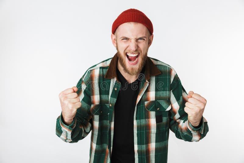 Ritratto del cappello emozionante dell'uomo 20s e della camicia di plaid d'uso che gridano, mentre stando isolato sopra fondo bia immagine stock