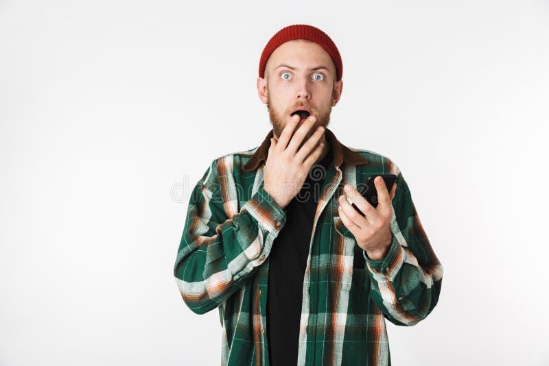 Ritratto del cappello del giovane e della camicia di plaid d'uso facendo uso del telefono cellulare, mentre stando isolato sopra  fotografia stock libera da diritti