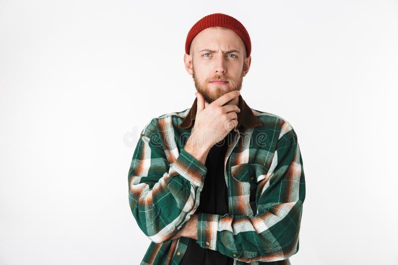 Ritratto del cappello del tipo europeo e della camicia di plaid d'uso che toccano il suo mento, mentre stando isolato sopra fondo fotografia stock