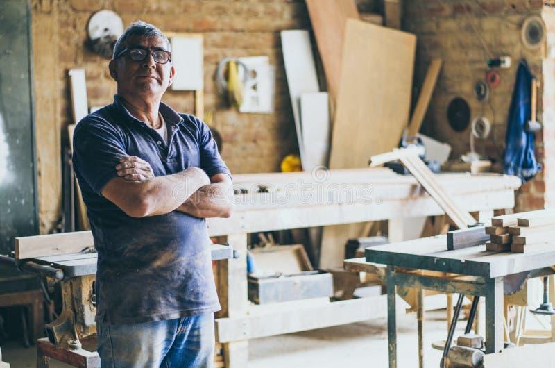 Ritratto del carpentiere senior nella sua officina e di esame della macchina fotografica immagine stock