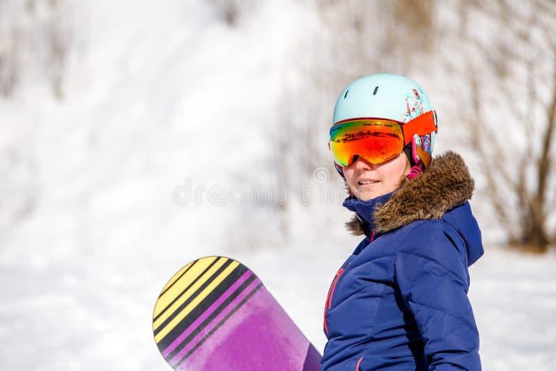 Ritratto del casco d'uso della donna sportiva con lo snowboard immagine stock libera da diritti