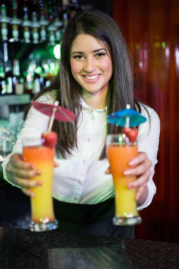 Ritratto del cocktail grazioso del servizio del barista al contatore della barra fotografie stock libere da diritti