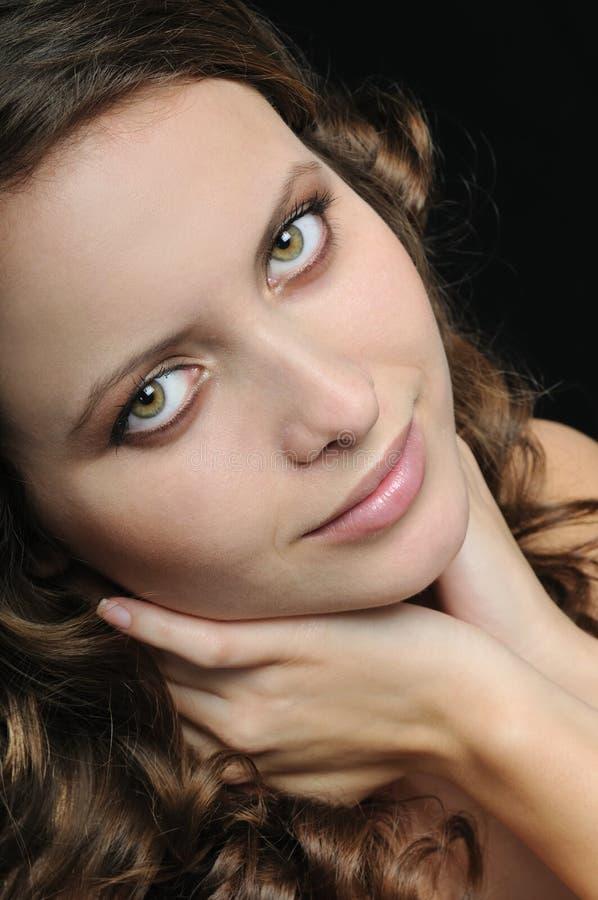 Ritratto del collo della holding della giovane donna sul nero fotografia stock
