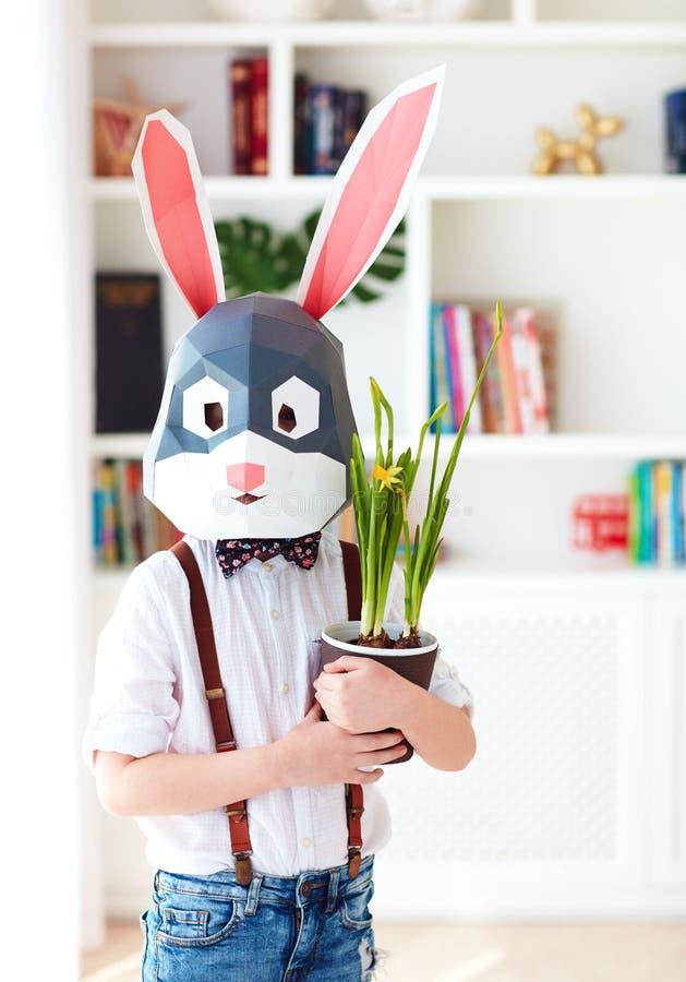 Ritratto del coniglio poligonale alla moda con i fiori conservati in vaso di una molla fresca, maschera poligonale di pasqua fotografia stock