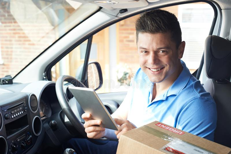 Ritratto del corriere With Digital Tablet in Van Delivering Package To House immagini stock libere da diritti