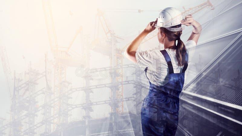 Ritratto del costruttore in un casco sul fondo della città immagine stock