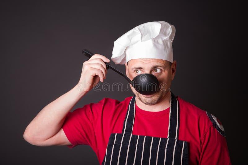 Ritratto del cuoco divertente con una siviera in sua mano fotografie stock