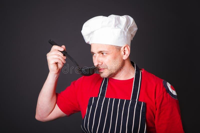 Ritratto del cuoco divertente con una siviera in sua mano fotografia stock