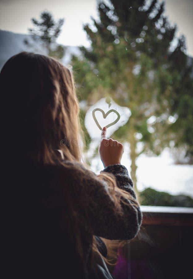 Ritratto del cuore del disegno della bambina sulla finestra congelata fotografie stock