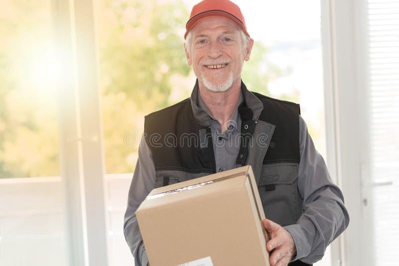 Ritratto del deliverer senior sorridente, effetto della luce immagini stock