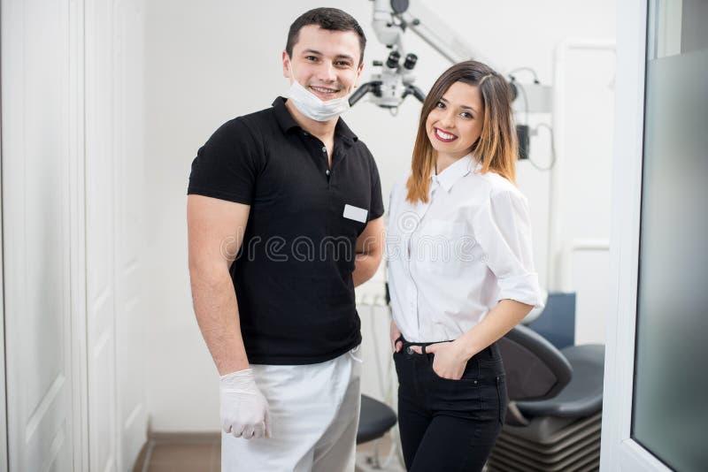 Ritratto del dentista maschio amichevole con il paziente femminile felice in clinica dentaria moderna odontoiatria fotografia stock