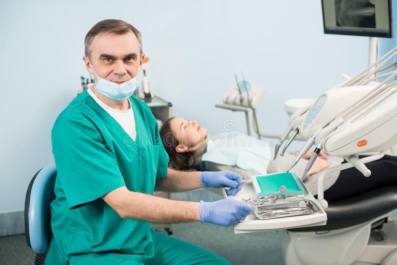 Ritratto del dentista maschio senior con gli strumenti dentari nell'ufficio dentario fotografie stock