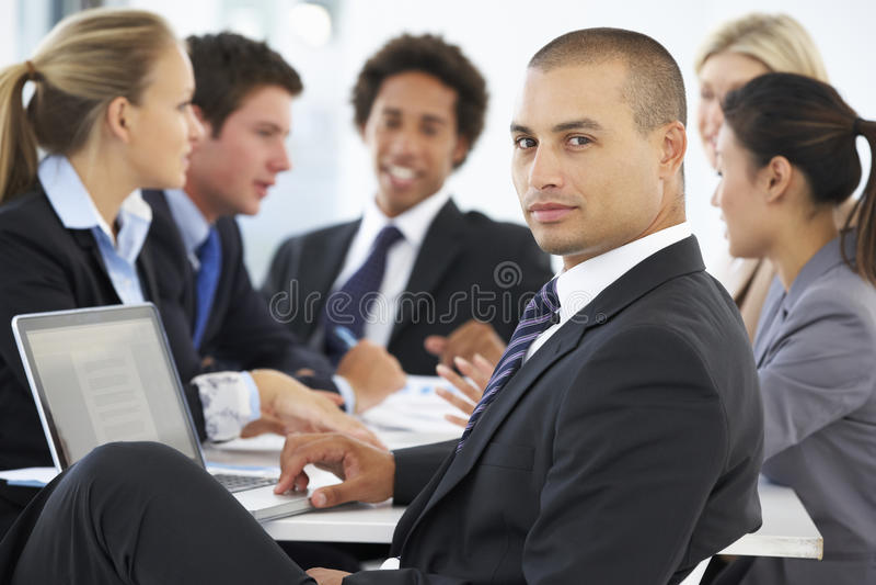 Ritratto del dirigente maschio con la riunione dell'ufficio nel fondo immagini stock