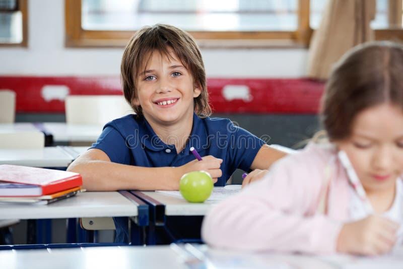 Ritratto del disegno felice dello scolaro all'aula fotografie stock libere da diritti