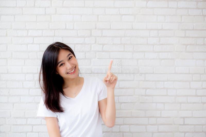 Ritratto del dito diritto di bella giovane felicità asiatica della donna che indica qualcosa su struttura grigia del cemento immagine stock libera da diritti