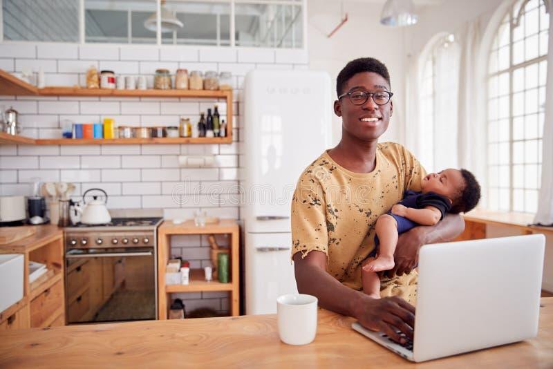 Ritratto del figlio a funzioni multiple e di lavorare di Holding Sleeping Baby del padre al computer portatile in cucina immagini stock