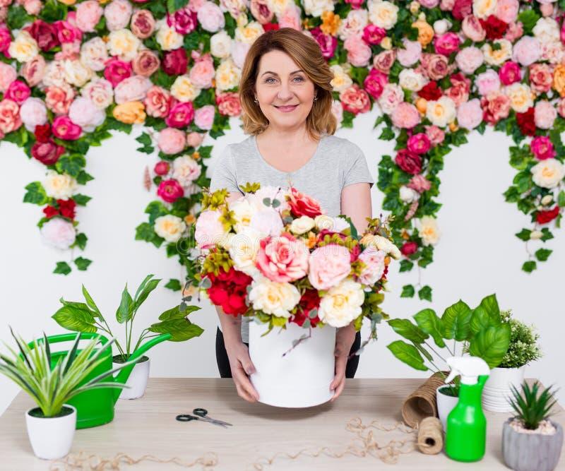 Ritratto del fiorista maturo sorridente della donna che lavora nel negozio di fiore immagini stock