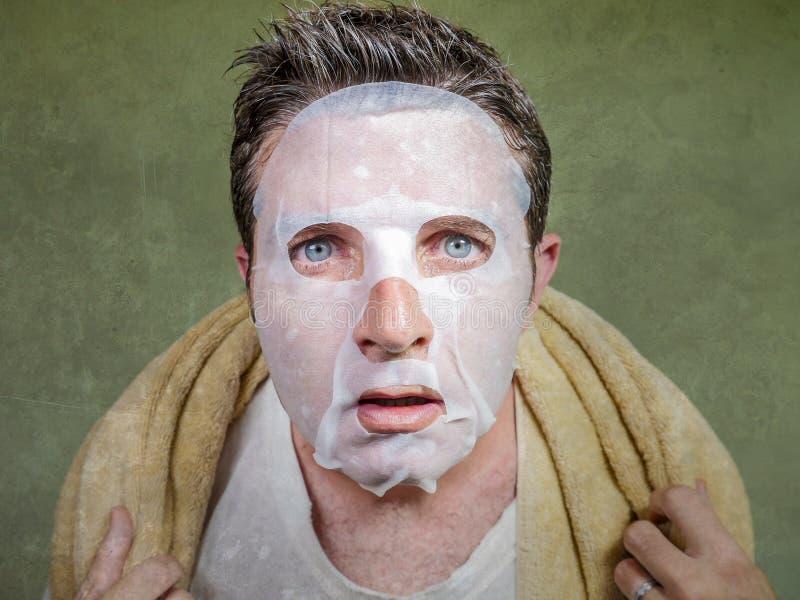 Ritratto del fondo isolato stile di vita di giovane uomo strano e divertente a casa che prova facendo uso della pulizia facciale  fotografie stock libere da diritti