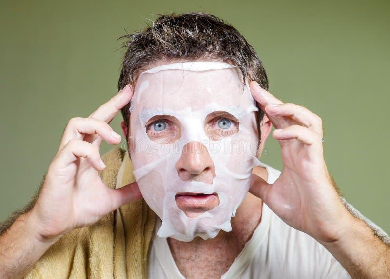 Ritratto del fondo isolato stile di vita di giovane uomo strano e divertente a casa che prova facendo uso della pulizia facciale  fotografia stock libera da diritti