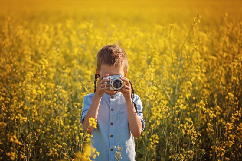 Ritratto del fotografo del ragazzino con la macchina fotografica sul fondo del campo di giallo tramonto immagine stock