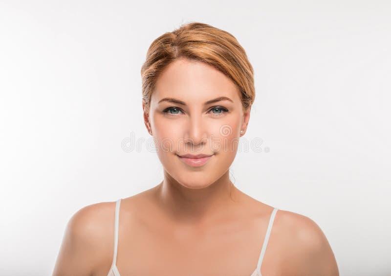 Ritratto del fronte della donna di bellezza Macchina fotografica di sguardo femminile bionda su un fondo bianco immagine stock